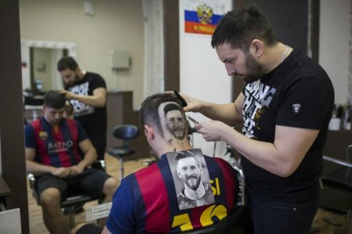 Serbian hairdresser Mario Hvala creates a portrait of Argentinian star Lionel Messi with the hair a World Cup football fan in Novi Sad, June 10, 2018