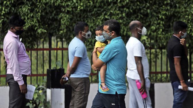 Seorang pria menggendong anak saat menunggu untuk berkonsultasi dengan dokter di fasilitas skrining COVID-19 di Jammu, India, Jumat (17/7/2020). India melewati 1 juta kasus virus corona COVID-19 atau tertinggi ketiga di dunia setelah Amerika Serikat dan Brasil. (AP Photo/Channi Anand)