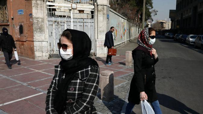 Warga Iran terlihat memakai masker sebagai upaya perlindungan dari Virus Corona yang telah menyebar luas di negara tersebut. (AP/ Vahid Salemi)