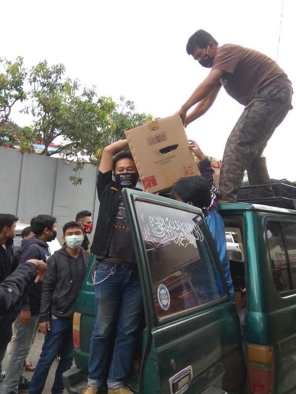 Puluhan remaja Solidarity Community (SC) 234 Garut, Jawa Barat, tengah bahu membahu menurunkan puluhan paket sembako yang akan dibagikan bagi masyarakat miskin perkotaan di Garut. (Liputan6.com/Jayadi Supriadin)