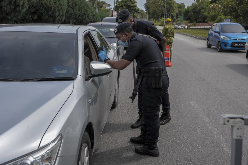 Policemen conduct checks on vehicles at a roadblock at Taman Sri Andalas in Klang October 10, 2020. — Picture by Shafwan Zaidon