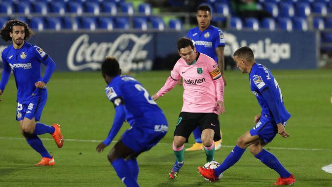 Striker Barcelona, Lionel Messi, berusaha melewati pemain Getafe pada laga Liga Spanyol di Stadion Coliseum Alfonso Perez, Minggu (18/10/2020). Barcelona takluk dengan skor 1-0. (AP/Manu Fernandez)