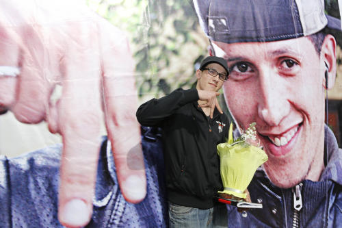 "Mouad Belghouat known as el-Haqed or ""the Enraged,"" poses with flowers received from activists after a press conference at the old slaughterhouse in Casablanca, Friday March 29, 2013. The Moroccan rapper, known for his social activism and protest songs, said he will concentrate on his music and studies after being released from prison for insulting police. (AP Photo/Abdeljalil Bounhar)"