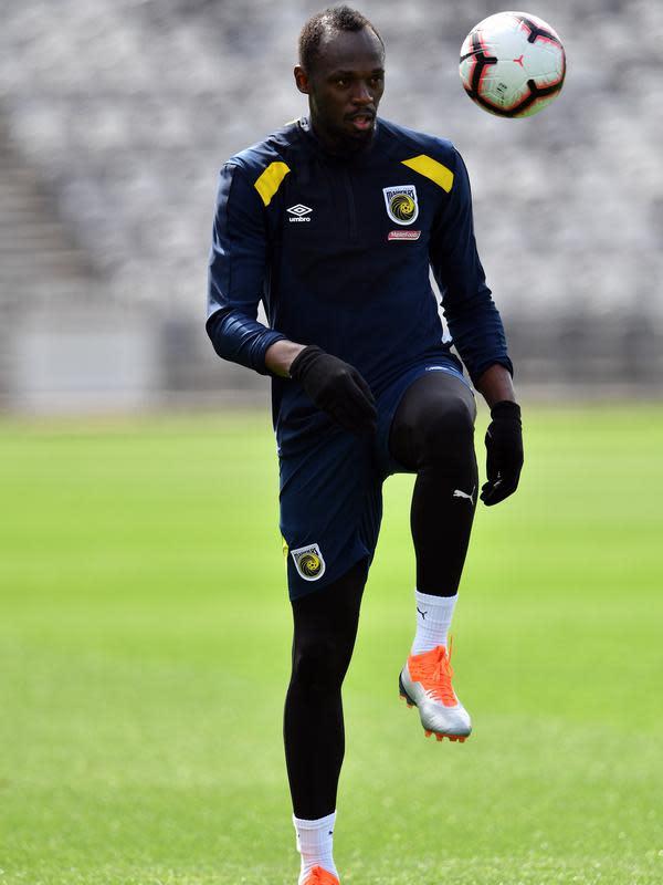 Usain Bolt menjuggling bola saat latihan di Central Coast Stadium, Gosford, Australia, (21/8). Pria yang (21/8) ini berulang tahun ke-32 dijadwalkan bermain di klub divisi pertama untuk mendapatkan rekomendasi kontrak berikutnya. (AFP Photo/Saeed Khan)