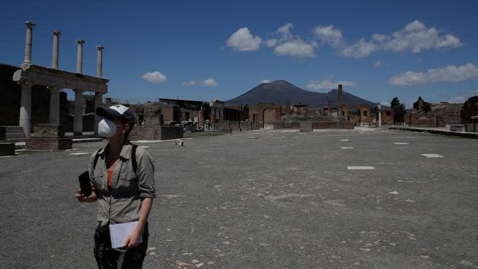Seorang jurnalis mengunjungi situs arkeologi Pompeii seusai kebijakan lockdown selama dua bulan untuk mengendalikan penyebaran Covid-19 di Italia, Selasa (26/5/2020). Salah satu situs arkeologi paling terkenal di dunia ini dibuka kembali untuk umum pada 26 Mei. (AP Photo/Alessandra Tarantino)