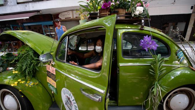 Roberta Machado dari Brasil duduk di Volkswagen Beetle 1969 miliknya yang diubah menjadi toko bunga keliling di Copacabana, Rio de Janeiro, Rabu (14/10/2020). Perempuan 51 tahun ini mengubah VW kodok untuk bertahan dari krisis akibat pandemi COVID-19. (MAURO PIMENTEL/AFP)