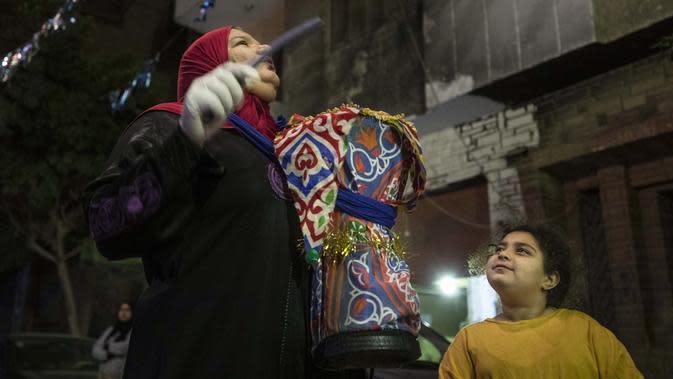 Seorang mesaharati Hajja Dalal (46) membangunkan warga untuk sahur saat bulan suci Ramadan di Kairo, Mesir, Rabu (29/4/2020). Tradisi mesaharati terus berlanjut hingga zaman modern, yang berlangsung hampir 600 tahun. (AP Photo/Nariman El-Mofty)