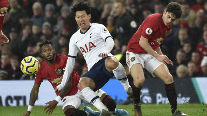 Penyerang Tottenham Hotspur, Son Heung-min saat dilanggar dua pemain Manchester United, Fred dan Daniel James pada pertandingan lanjutan Liga Inggris di Old Trafford, Rabu (4/12/2019). MU menang tipis atas Tottenham 2-1. (AP Photo/Rui Vieira)