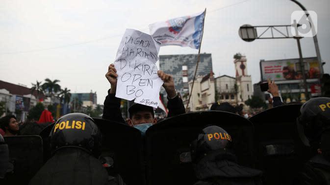 Pengunjuk rasa mengangkan poster saat berdemonstrasi menolak UU Cipta Kerja di kawasan Harmoni, Jakarta, Kamis (8/10/2020). UU Cipta Kerja yang disahkan beberapa waktu lalu memicu demonstasi sejumlah kalangan. (Liputan6.com/Faizal Fanani)
