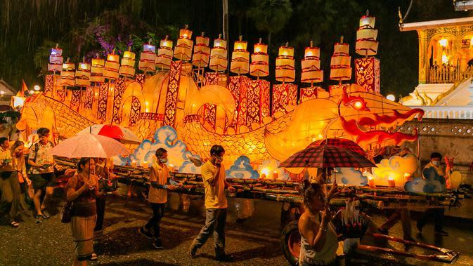 Warga mengikuti parade bersama perahu naga di Luang Prabang, Laos, 3 Oktober 2020. Dalam Festival Boun Lai Heua Fai, warga mendandani kota dengan berbagai lentera, berparade bersama, kemudian melarungkan perahu naga besar dan kecil dari batang pohon pisang ke Sungai Mekong. (Xinhua/Kaikeo Saiyasane)
