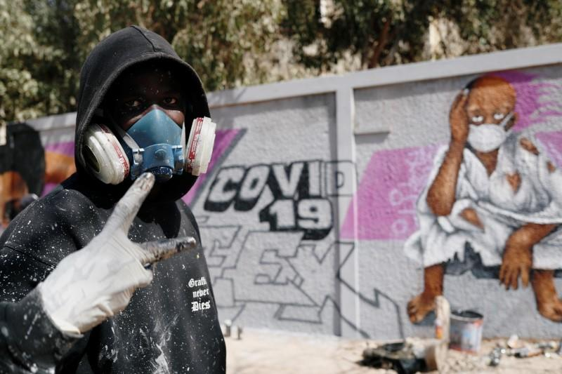 Serigne Boye aka Zeus, a graffiti artist from RBS crew reacts as he stands beside his mural, that he was working on to encourage people to protect themselves amid the outbreak of the coronavirus disease (COVID-19), in Dakar