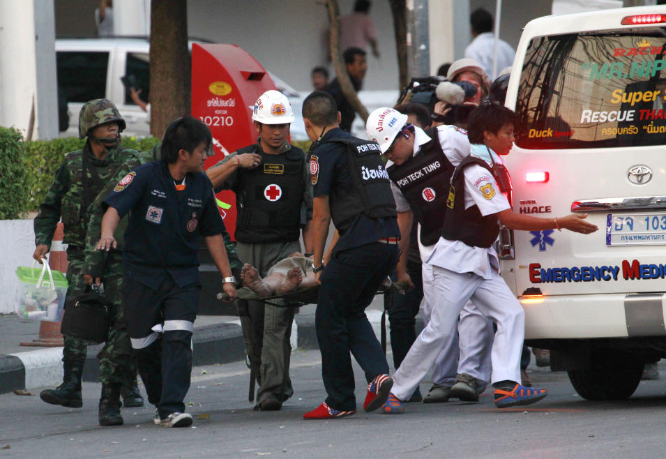 Charity workers carry a man who was wounded from a gun shot on a stretcher to an ambulance following clashes between anti and pro-government groups in Bangkok, Thailand, Saturday, Feb. 1, 2014. Gunfire rang out at a major intersection in Thailand's capital on Saturday as clashes between protesters and government supporters erupted on the eve of tense nationwide elections. At least seven people are reported wounded, including an American photojournalist. (AP Photo/Wason Wanichakorn)