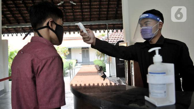 Petugas memeriksa suhu tubuh salah seorang pekerja saat hendak memasuki Museum Kebangkitan Nasional, Jakarta, Senin (8/6/2020). Pengelola menyiapkan standar protokol kesehatan jelang dibuka kembali untuk umum saat masa PSBB Transisi guna memutus penyebaran Covid-19. (merdeka.com/Iqbal S Nugroho)