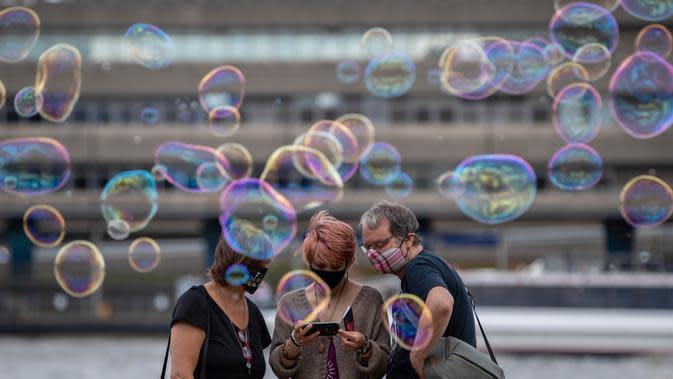 Orang-orang yang mengenakan masker melihat-lihat foto hasil jepretan di tepi Sungai Thames di London, Inggris, 1 Agustus 2020. Pemerintah Inggris pada Jumat (31/7) mengumumkan penundaan pelonggaran beberapa langkah pembatasan menyusul jumlah infeksi virus corona yang meningkat. (Xinhua/Han Yan)