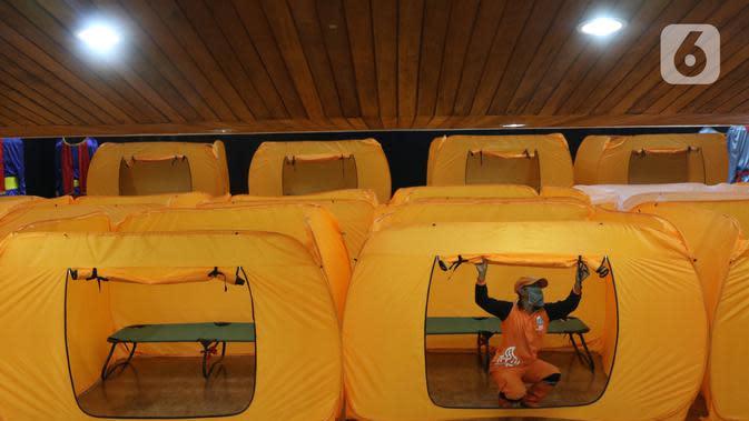 RUANG ISOLASI COVID-19: Petugas merapihkan tenda yang akan dijadikan tempat isolasi Covid-19 di gedung kesenian Tanah Abang, Jakarta, Minggu (17/5/2020). Gedung ini dijadikan tempat isolasi bagi masyarakat yang akan mengikuti rapid test esok dilokasi tersebut. (Liputan6.com/Angga Yuniar)