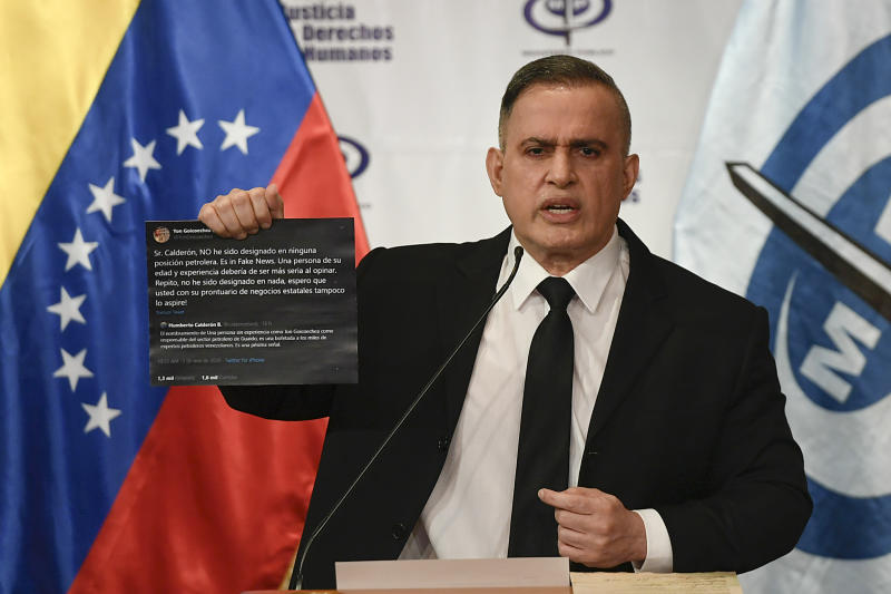 Venezuela's Attorney General Tarek William Saab holds up twitter posts during a press conference regarding what the government calls a failed attack over the weekend aimed at overthrowing President Nicolás Maduro in Caracas, Venezuela, Monday, May 4, 2020. The twitter posts are between two members of the opposition, Humberto Calderon and Yon Goicoechea.  (AP Photo/Matias Delacroix)