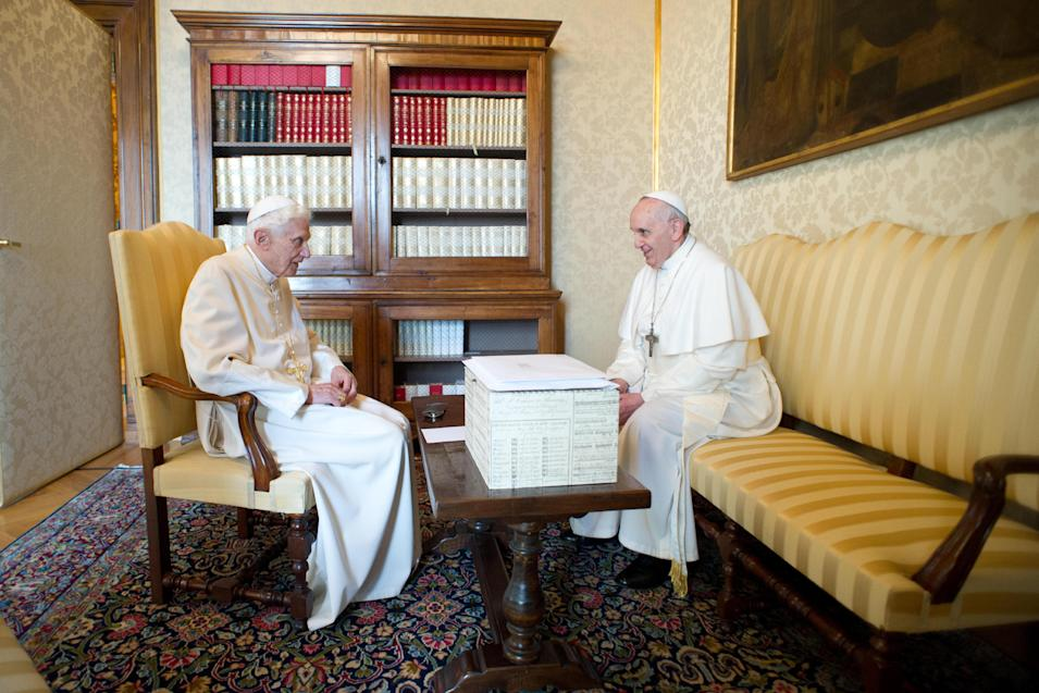 """In this photo provided by the Vatican paper L'Osservatore Romano, Pope Francis, right, and Pope emeritus Benedict XVI meet in Castel Gandolfo Saturday, March 23, 2013. Pope Francis has traveled to Castel Gandolfo to have lunch with his predecessor Benedict XVI in a historic and potentially problematic melding of the papacies that has never before confronted the Catholic Church. The Vatican said the two popes embraced on the helipad. In the chapel where they prayed together, Benedict offered Francis the traditional kneeler used by the pope. Francis refused to take it alone, saying """"We're brothers,"""" and the two prayed together on the same one. (AP Photo/Osservatore Romano, HO)"""