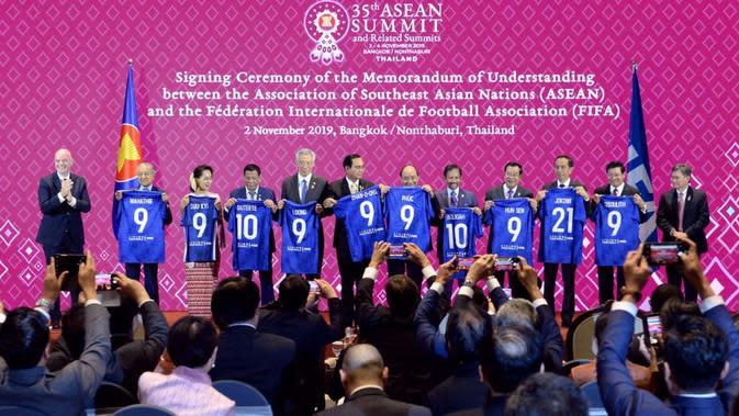 Presiden Jokowi bersama kepala negara dan kepala pemerintahan negara-negara ASEAN menunjukkan jersey bertuliskan nama masing-masing disaksikan Presiden FIFA Gianni Infantino (kiri) pada acara penandatanganan MoU antara ASEAN dengan FIFA di Bangkok, Sabtu (2/11/2019). (Liputan6.com/Biro Pers Setpres)