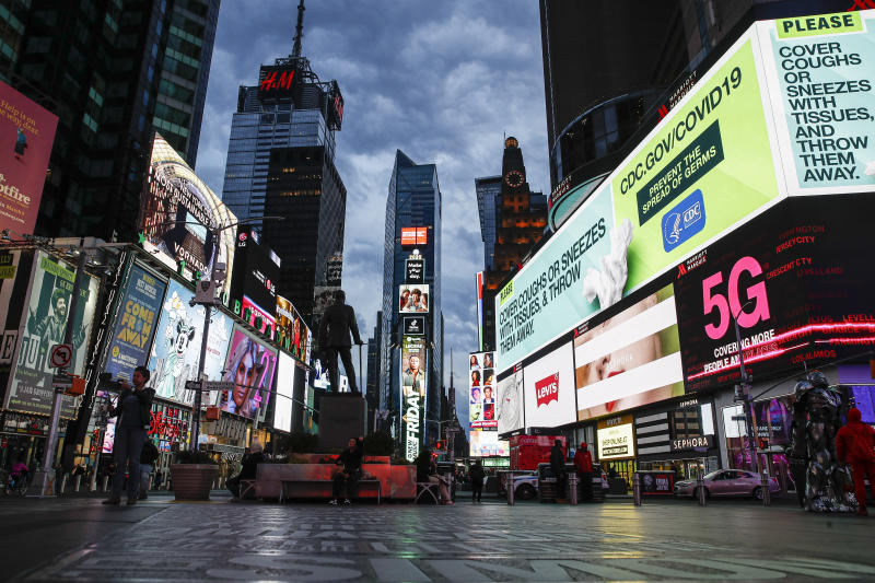 "A screen displaying messages concerning COVID-19 is seen in a sparsely populated Times Square, Friday, March 20, 2020, in New York. New York Gov. Andrew Cuomo is ordering all workers in non-essential businesses to stay home and banning gatherings statewide. ""Only essential businesses can have workers commuting to the job or on the job,"" Cuomo said of an executive order he will sign Friday. Nonessential gatherings of individuals of any size or for any reason are canceled or postponed. (AP Photo/John Minchillo)"