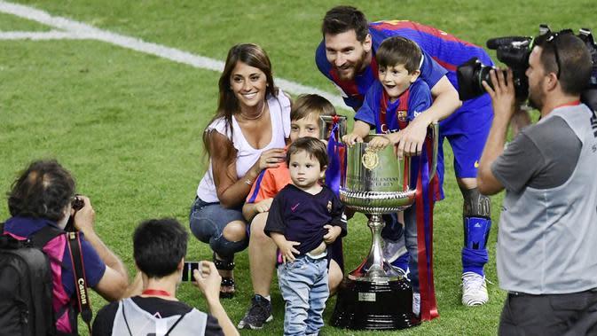 Bintang Barcelona, Lionel Messi bersama Antonella Roccuzzo dan anak-anaknya berpose saat merayakan gelar juara Copa Del Rey di Stadion Vicente Calderon, (27/5/2017). (AFP/Javier Soriano)