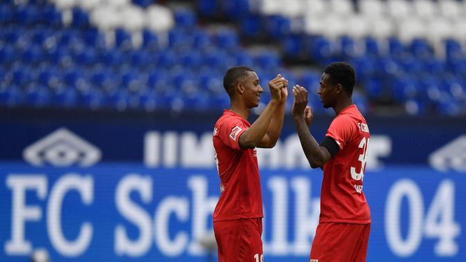 Pemain Augsburg, Felix Uduokha dan Reece Oxford merayakan kemenangan atas Schalke 04 pada laga Bundesliga di Veltins-Arena, Minggu (24/5/2020). Augsburg menang dengan skor 3-0 atas Schalke 04. (AP/Martin Meissner)