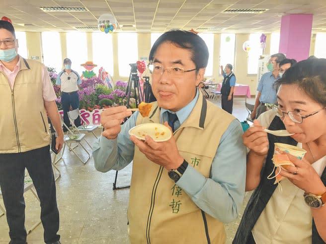 台南市長黃偉哲不顧鏡頭當前,大口吃下以台南好米製成的米布丁。(周書聖攝)