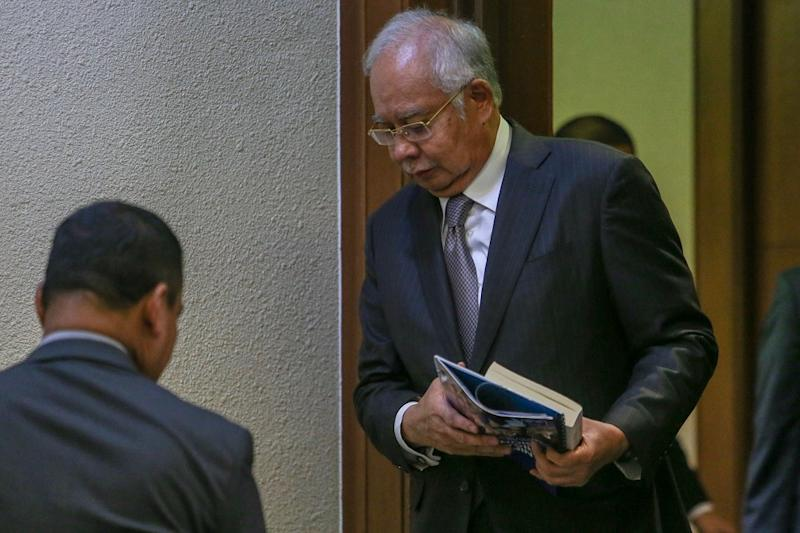 Datuk Seri Najib Razak walks out of the courtroom during lunch break of day 16 of his trial, with a book and what is believed to be BN's GE14 manifesto hidden underneath in his hands, in Kuala Lumpur May 9, 2019. — Picture by Hari Anggara