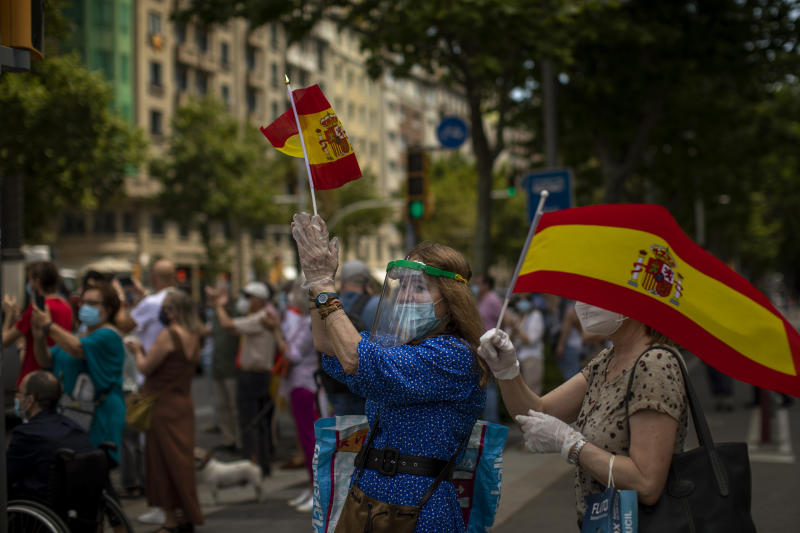People applaud at demonstrators during a drive-in protest organised by Spain's far-right Vox party against the Spanish government's handling of the nation's coronavirus outbreak in Barcelona, Spain, Saturday, May 23, 2020.  (AP Photo/Emilio Morenatti)
