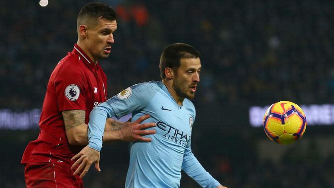 Gelandang Manchester City, David Silva berusaha mengontrol bola dari kawalan bek Liverpool, Dejan Lovren pada pertandingan lanjutan Liga Inggris di stadion Etihad (3/1). City menang tipis atas Liverpool 2-1. (AP Photo/Dave Thompson)