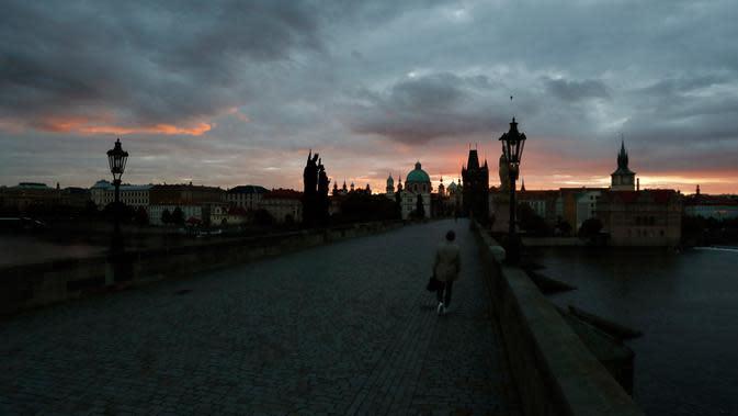 Seorang pria melintasi Jembatan Charles yang dibangun pada abad pertengahan di Praha, Republik Ceko, Kamis (8/10/2020). Ceko adalah salah satu negara terparah di Eropa Tengah dan Timur yang mengkonfirmasi lonjakan rekor infeksi COVID-19 selama beberapa pekan terakhir. (AP Photo/Petr David Josek)
