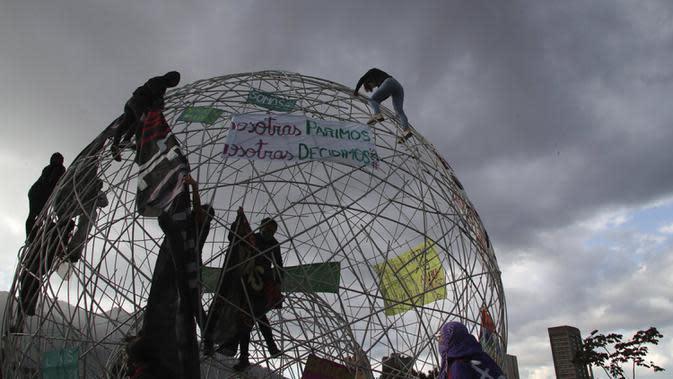 Sejumlah perempuan memasang spanduk pada sebuah bola di Taman Arbolito selama protes hak-hak aborsi di Quito, Ekuador, Senin (28/9/2020). (AP Photo/Dolores Ochoa)