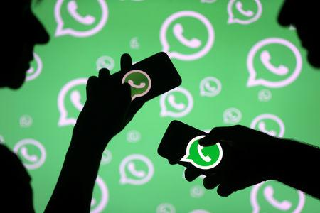 FILE PHOTO: Men pose with smartphones in front of displayed Whatsapp logo in this illustration