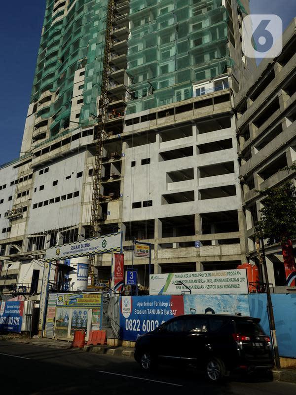 Kendaraan melintas di depan proyek pembangunan apartemen di Stasiun Tanjung Barat, Jakarta, Sabtu (22/2/2020). Apartemen alisan hunian vertical yang terintegrasi dengan pusat perbelanjaan serta perkantoran menjadi pilihan kaum urban dari kalangan profesional muda. (merdeka.com/Imam Buhori)