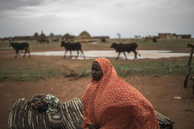 The long trail: Safira, a nomadic herder, sits on a straw mat outside her family hut in a Fulani camp in Dosso