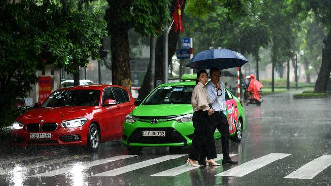 Pejalan kaki menyeberang jalan saat hujan deras di Hanoi (14/10/2020). Badai tropis Nangka menghantam Vietnam tengah-utara yang mengakibatkan bencana alam, terutama hujan lebat dan banjir, telah menyebabkan 28 orang tewas dan 12 lainnya hilang. (AFP Photo/Manan Vatsyayana)