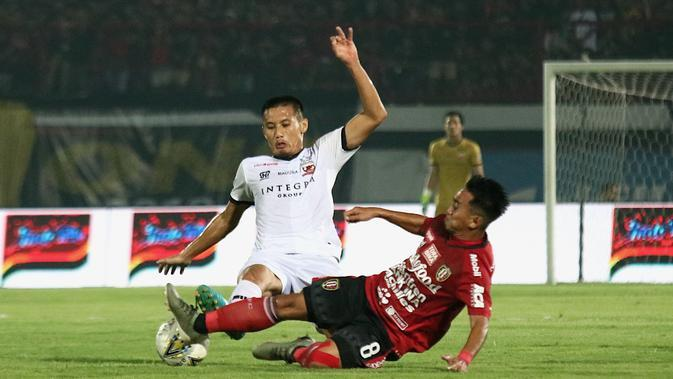Gelandang Bali United, Muhammad Taufiq, berebut bola dengan gelandang Madura United, Guntur Ariyadi, pada laga Liga 1 2019 di Stadion Kapten I Wayan Dipta, Bali, Minggu (22/12). Bali kalah 0-2 dari Madura. (Bola.com/Aditya Wany)