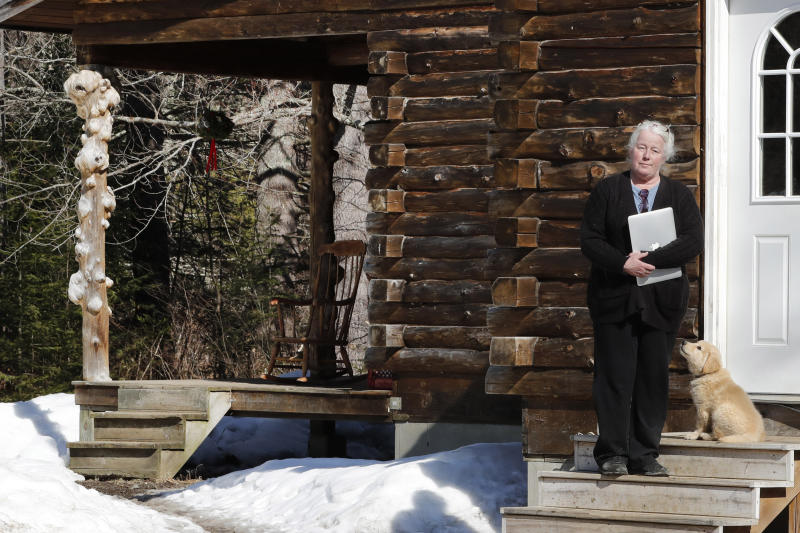 """Julie Dolan, chair of her town's Broadband Committee, poses with her computer on the steps of her family's rural home in Sandwich, N.H., Thursday, March 26, 2020.  In the town of 1,200 best known as the setting for the movie """"On Golden Pond,"""" broadband is scarce. Forget streaming Netflix, much less working or studying from home. Even the police department has trouble uploading its reports.    (AP Photo/Charles Krupa)"""