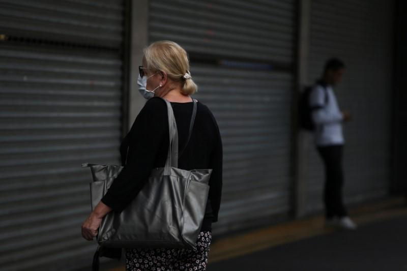 A woman wearing a face mask stands in front a closed mall that reduced its opening hours amid the coronavirus disease (COVID-19) outbreak in Sao Paulo