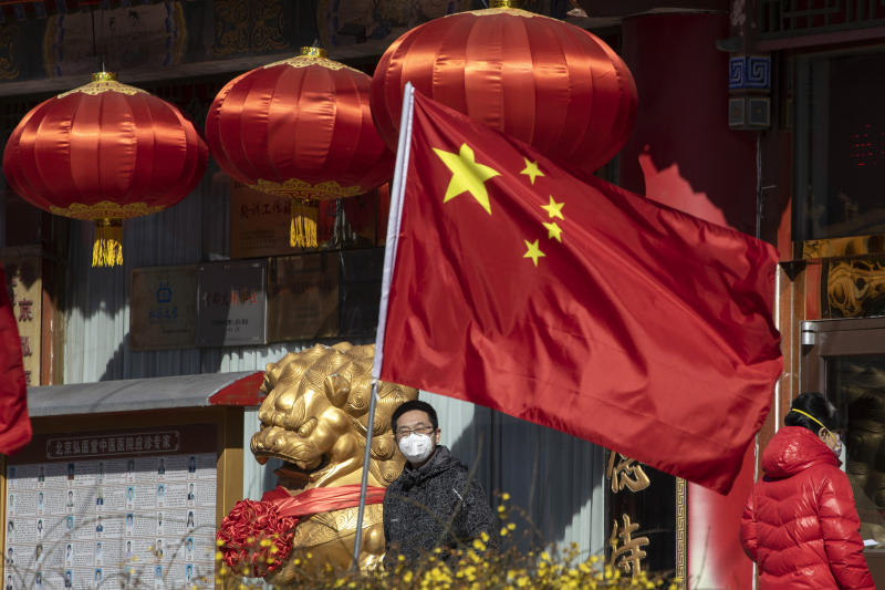 A masked man looks out near a national flag outside a traditional medicine hospital in Beijing on Tuesday, March 3, 2020. Mushrooming outbreaks in the Mideast, Europe and South Korea contrasted with optimism in China, where thousands of recovered patients were going home and new virus cases drop to a new low. (AP Photo/Ng Han Guan)