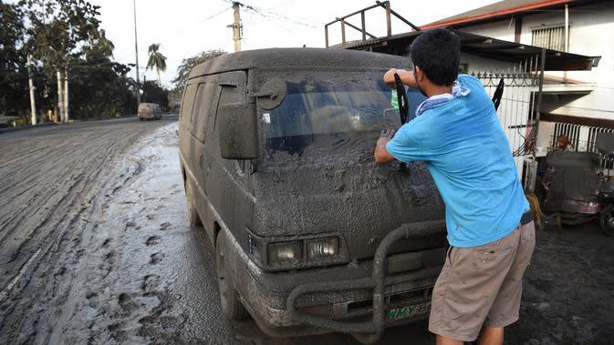 Warga membersihkan abu vulkanik dari kendaraan mereka setelah erupsi Gunung Taal di Tagaytay, Provinsi Cavite, Filipina, Senin (13/1/2020). Gunung yang terakhir meletus pada tahun 1977 tersebut melontarkan abu vulkanik mencapai 50.000 kaki (15.000 meter) ke atmosfer. (TED ALJIBE/AFP)