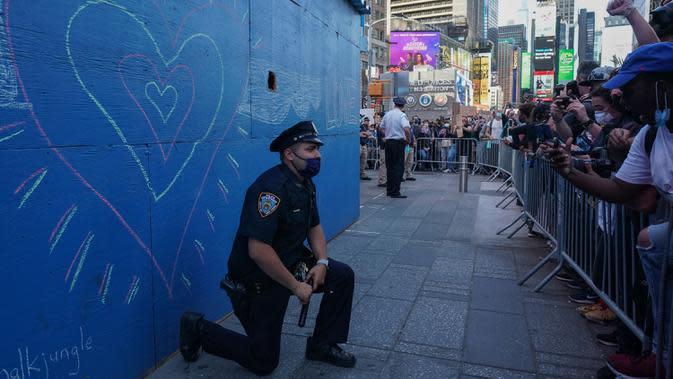 Seorang perwira polisi Kota New York berlutut saat pengunjuk rasa berdemonstrasi atas kematian George Floyd di Times Square, New York pada 31 Mei 2020. George Floyd, pria kulit hitam itu tewas tak bisa bernafas karena tercekik lutut polisi saat ditangkap pada (25/5/2020) lalu. (Bryan R. Smith / AFP)