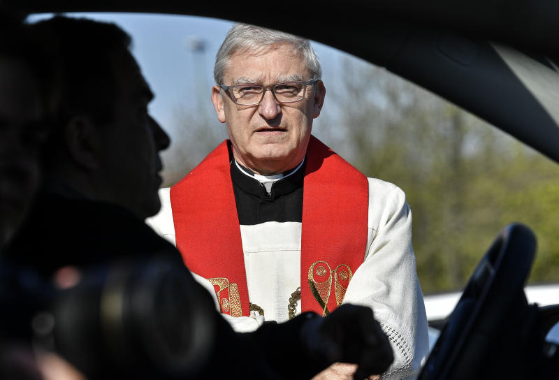 Priest Frank Heidkamp talks to believers in their cars prior a Good Friday church service at a drive-in cinema when all German churches are closed for worships due to the coronavirus outbreak in Duesseldorf, Germany, Friday, April 10, 2020. (AP Photo/Martin Meissner)