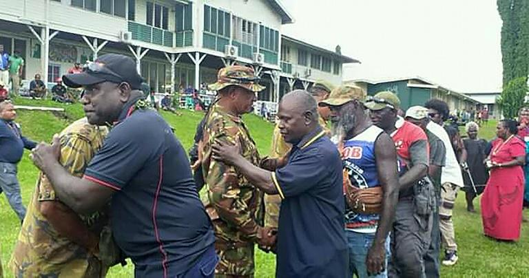 Former Bougainville Revolutionary Army fighters embrace Papua New Guinean policemen at a reconciliation ceremony in Kokopo in East New Britain