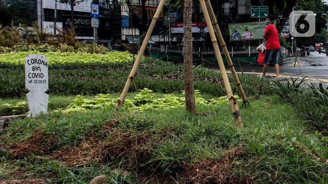 Warga melihat kuburan dengan papan nisan bertuliskan Corona bin Covid di taman Jalan Jatinegara Barat, Jakarta, Minggu (20/9/2020). Kuburan tersebut sengaja dibuat untuk mengingatkan masyarakat yang melintas akan bahaya virus Covid-19. (Liputan6.comm/Johan Tallo)
