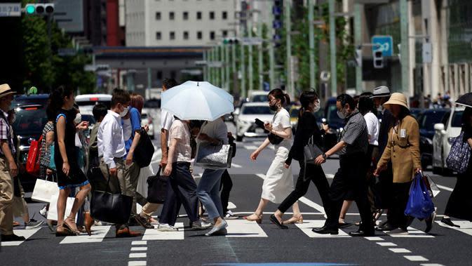Orang-orang menyeberang jalan di Tokyo, Jepang, Kamis (2/7/2020). Jepang mengangkat darurat pandemi selama tujuh minggu pada akhir Mei, sebagian besar kegiatan sosial dan bisnis sejak itu telah kembali dimulai. (AP Photo/Eugene Hoshiko)