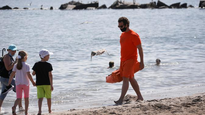 Seorang penjaga pantai berjalan di sebuah pantai di Coney Island, New York City, Amerika Serikat, pada 1 Juli 2020. Pada Rabu (1/7), delapan pantai di New York City secara resmi dibuka untuk berenang selama jam kerja harian penjaga pantai, yakni mulai pukul 10.00 hingga 18.00. (Xinhua/Wang Ying)