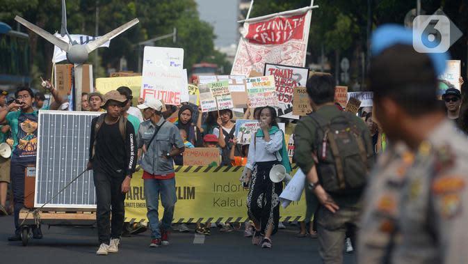 Aktivis lingkungan hidup dari berbagai LSM berjalan kaki menuju Taman Aspirasi di Istana Merdeka, Jakarta, Jumat (29/11/2019). Aktivis meminta pemerintah segera mendeklarasikan perubahan iklim yang semakin kritis. (merdeka.com/Imam Buhori)