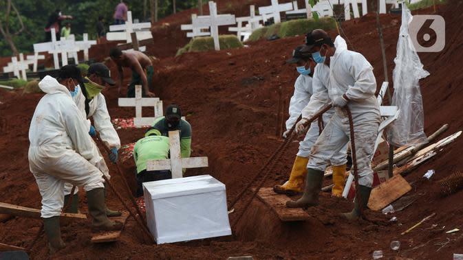 Petugas memakamkan jenazah dengan protokol COVID-19 di TPU Pondok Ranggon, Jakarta, Sabtu (17/10/2020). Pada Sabtu (17/10), 32 jenazah dimakamkan dengan protokol COVID-19 di TPU Pondok Ranggon. (Liputan6.com/Helmi Fithriansyah)