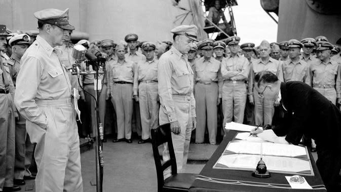 75 TAHUN BERAKHIRNYA PERANG DUNIA II: Jenderal AS Douglas MacArthur (kiri) menyaksikan Menteri Luar Negeri Jepang Manoru Shigemitsu menandatangani dokumen penyerahan di atas kapal perang USS Missouri, Teluk Tokyo, 2 September 1945. Ini menandai berakhirnya Perang Dunia II. (AP Photo/C.P. Gorry,File)