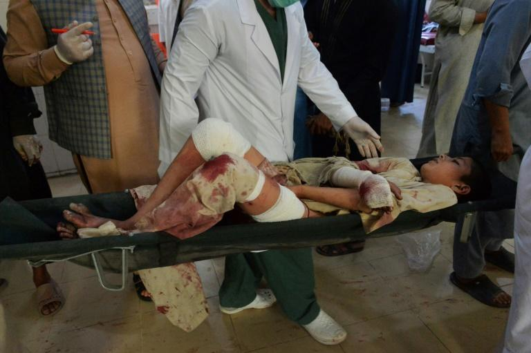 An injured boy is carried on a stretcher to hospital following the suicide attack at a funeral of a local police commander in Nangarhar